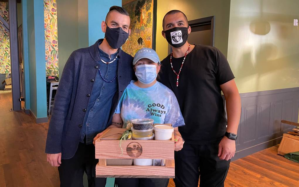 Cafe Ohlone owners Vincent Medina and Louis Trevino pose with Paula Callas, who is holding one of the restaurant's meal kit boxes.
