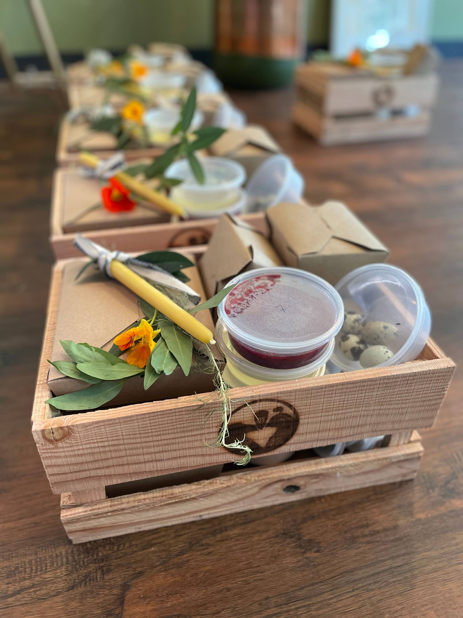 One of Cafe Ohlone's meal kits, packaged in a handmade wooden box, with fresh flowers and tubs of ingredients visible.