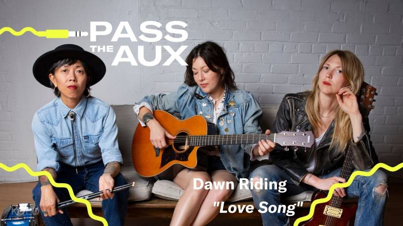 A musical trio dressed in denim sits on the couch; the woman on the left holds a drum stick, the one in the center strums an acoustic guitar and the one on the right holds an electric guitar.