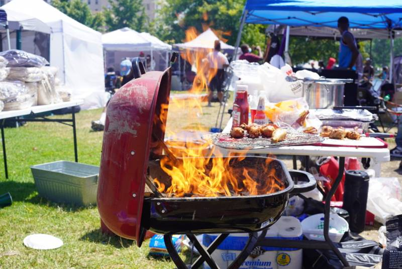 A barbecue grill is engulfed in flames near Lake Merritt as people celebrate Juneteenth in Oakland