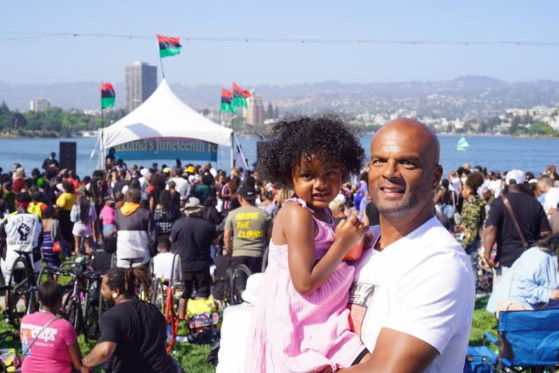 Travis Watts, organizer of Oakland's official Juneteenth celebration at Lake Merritt's amphitheater, is pictured with festival goers in the background as he holds his daughter Zaya.