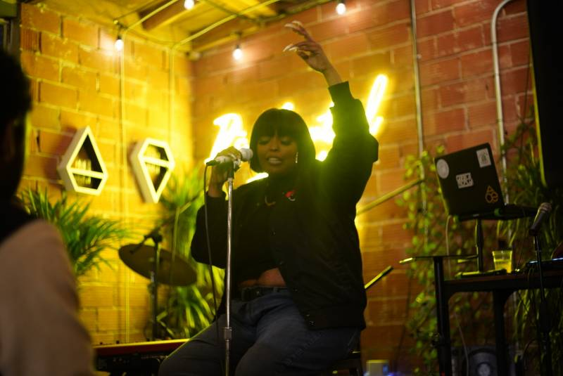 Jane Handcock raises her left arm as she vibes to her music while performing at Blk Girls Green House in West Oakland