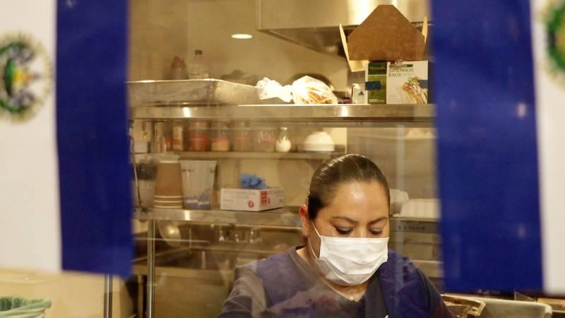 Estrella Gonzalez of Estrellita's Snacks prepares food in her commercial space at La Cocina kitchen while framed by the flag of El Salvador.