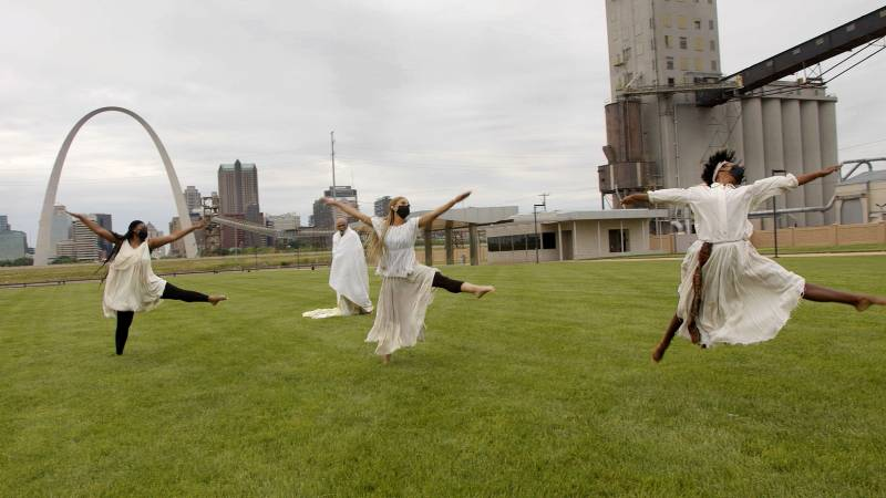 Three woman dancers on a grassy field, wearing matching off-white blouses and flowing white skirts, are in synchronized flying pose, against a backdrop of the St. Louis skyline and iconic St. Louis Gateway Arch.
