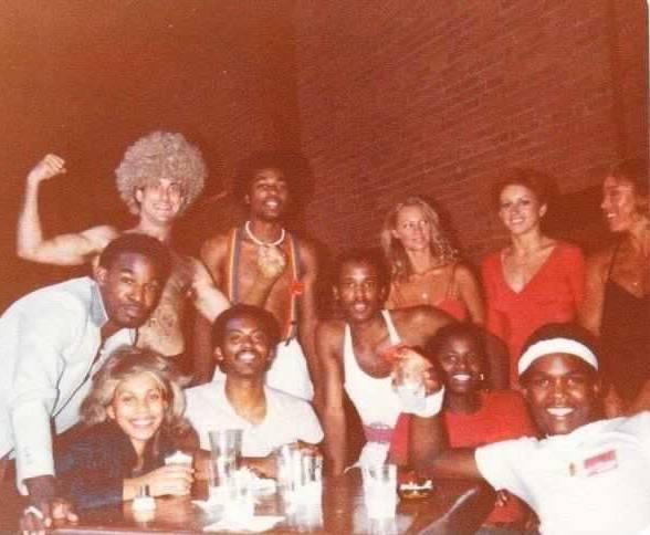 The cast of Dancing Wheels in 1979 at the end of a table, eleven of them stare into the camera. They are peak late seventies style, with big smiles.