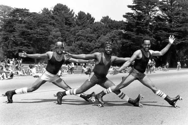 A black and white photo of The Golden Rollers. The three of them look like they are doing a Temptation-esque, in a diagonal formation striking a pose almost down in the splits -- really low to the ground --- with arms stretched out