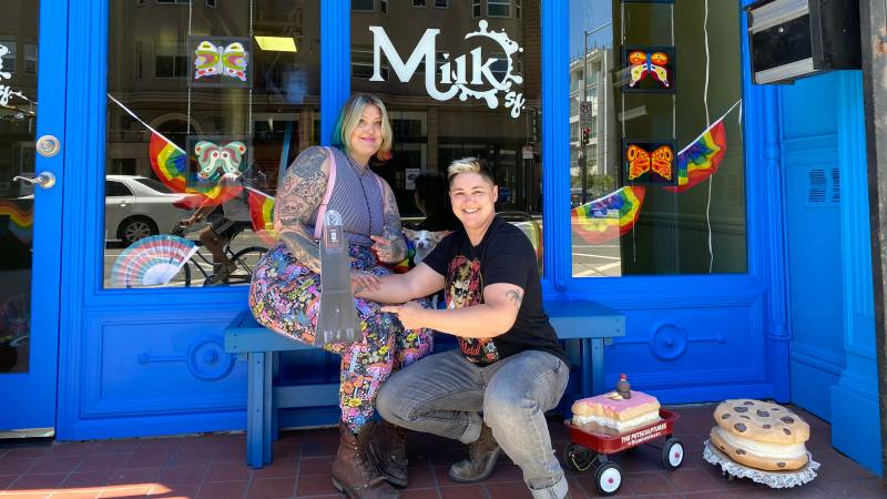 """Katey """"Scoots"""" McKee and Sharon Ratton in front of their Mission District coffee shop, Milk SF. There's a small red wagon with a sculpture of a birthday cake next to Ratton."""