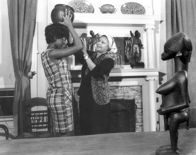 Katherine Dunham interacts with a visitor, who places a pot on her head, in her museum.