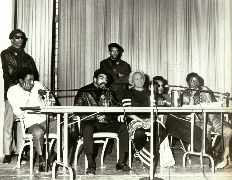 Katherine Dunham sits at a press conference table beside Reverend Charles Koen, Poet Eugene Redmond, and two members of the Black Eqyptians street gang.