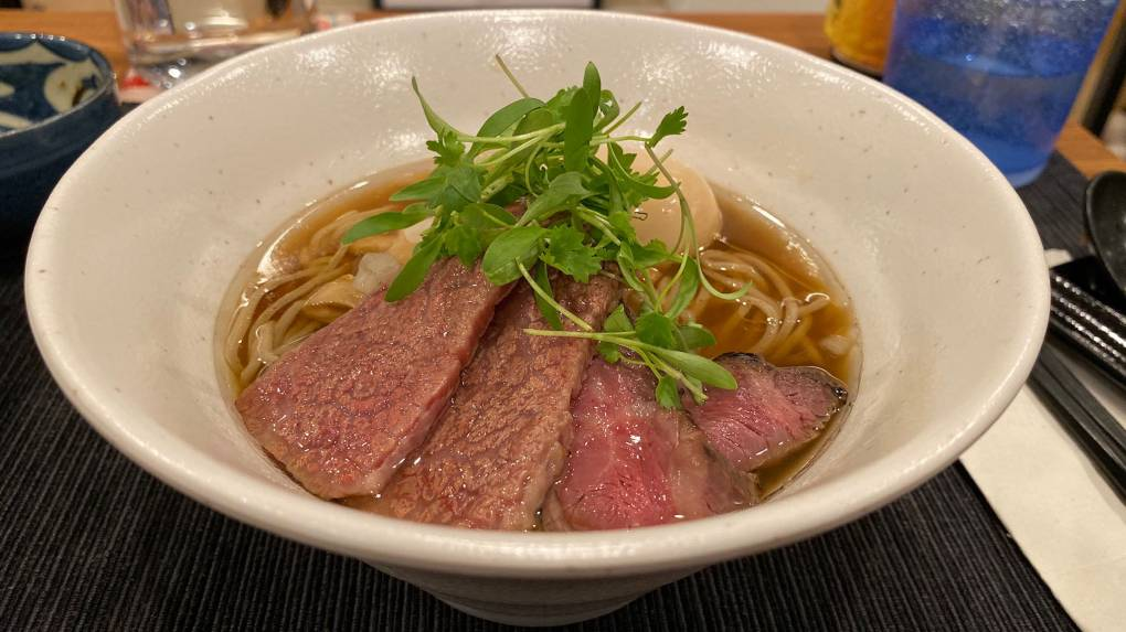 Bowl of ramen topped with slices of pink wagyu beef and a tangle of herbs.