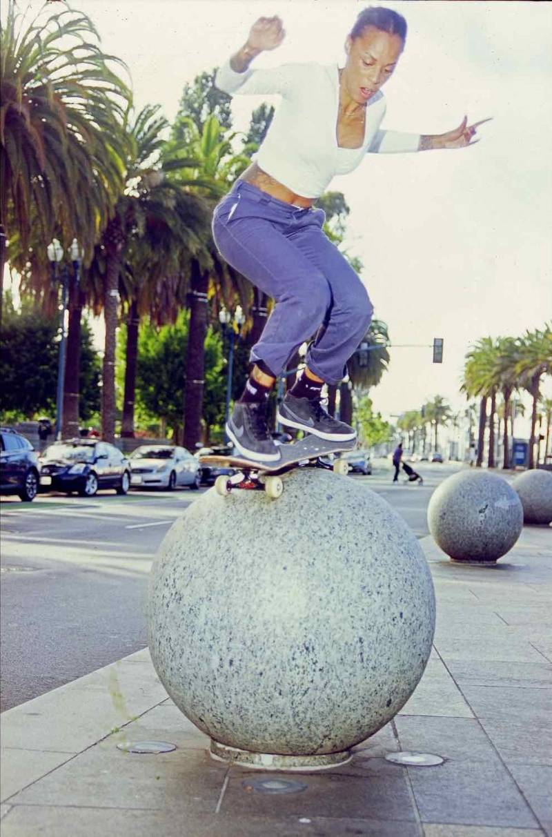 Marsha Howard balances on her skateboard atop a giant cement ball. Palm trees are in the background.