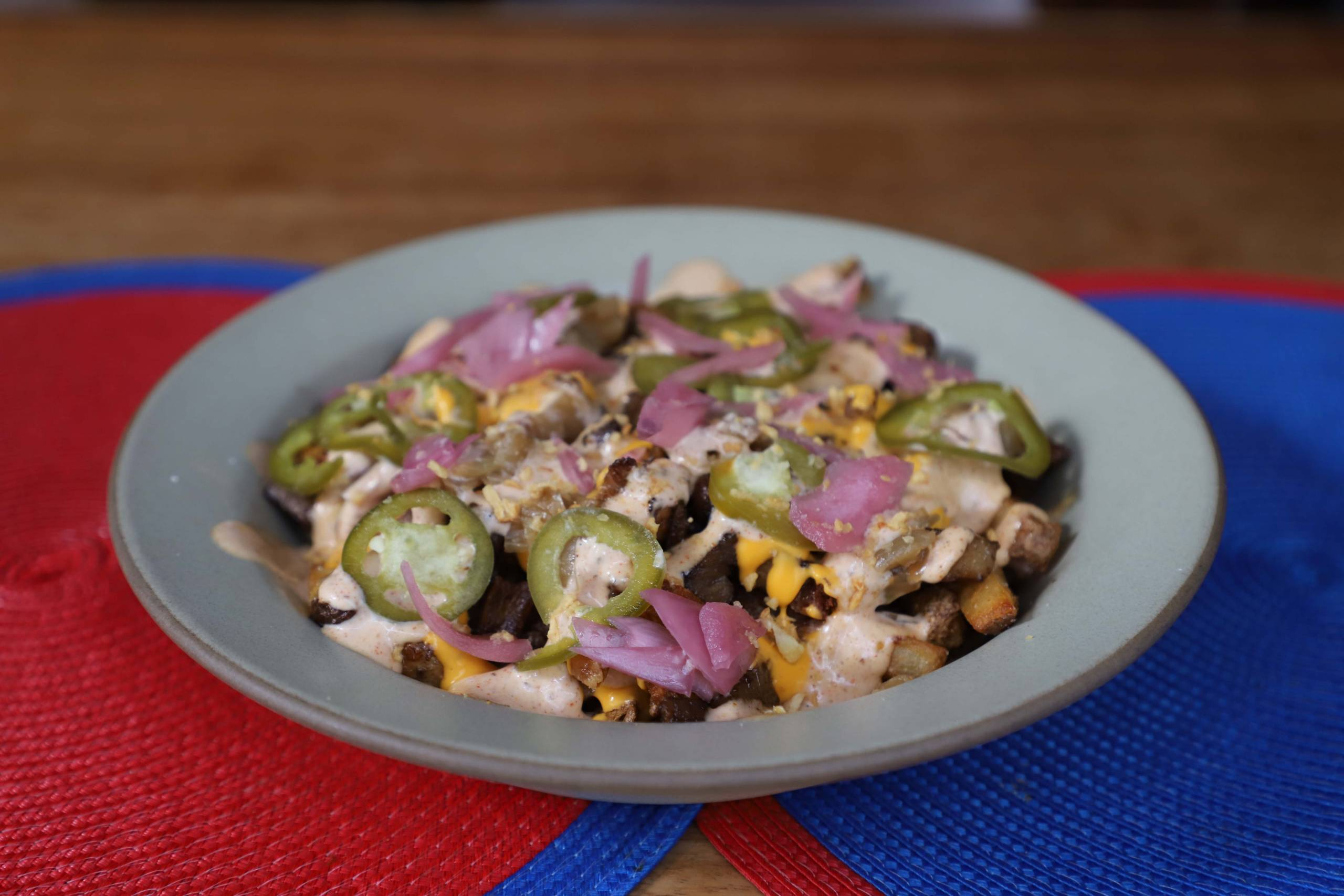 Kalye street fries, topped with onions, pickled jalapeños, pork sisig and Cheese Whiz