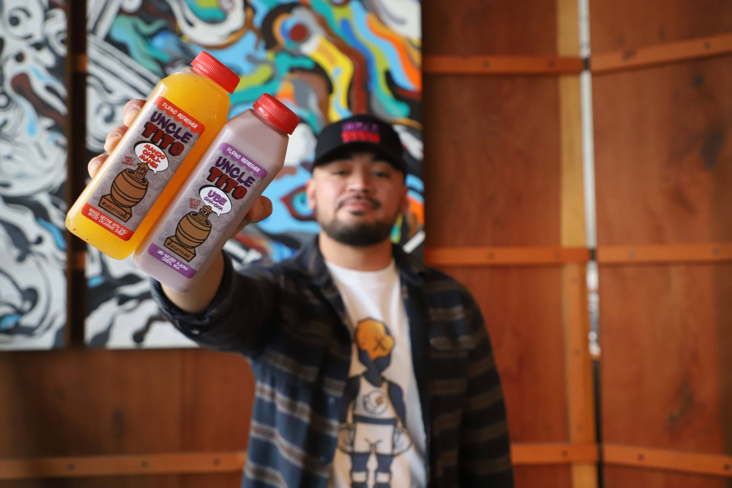 Joseph Alcasabas holds two of Uncle Tito's housemade beverages in his outstretched arm.