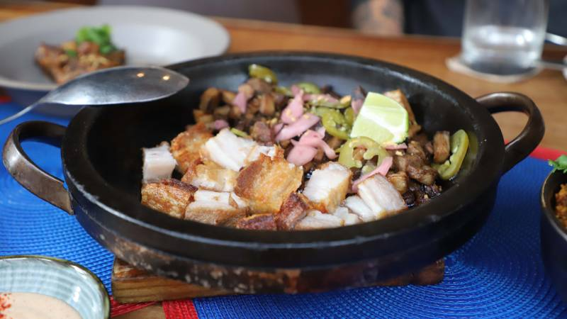 Crispy pork belly (lechon kawali) in a black skillet, topped with lime and pickled onions and jalapeños.