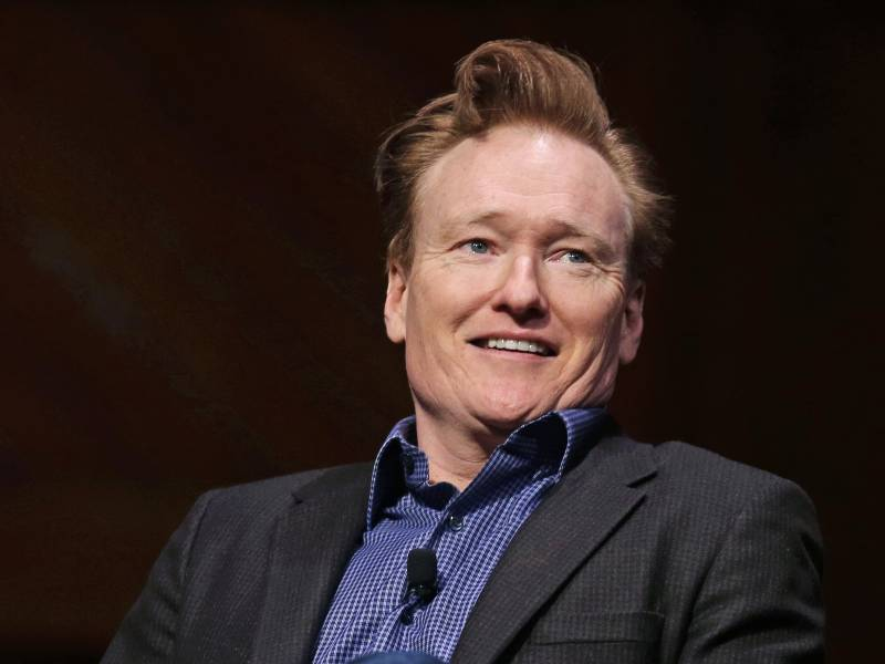 Conan O'Brien smiles towards an audience at Harvard University—his alma mater—in 2016.