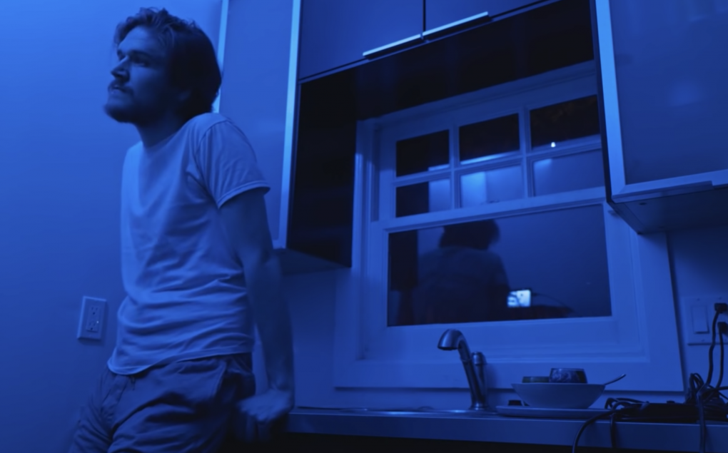 """Bo Burnham stands alone, pensively leaning on a kitchen sink. It's a moment from """"Facetiming With My Mom""""—part of his 'Inside' Netflix special."""