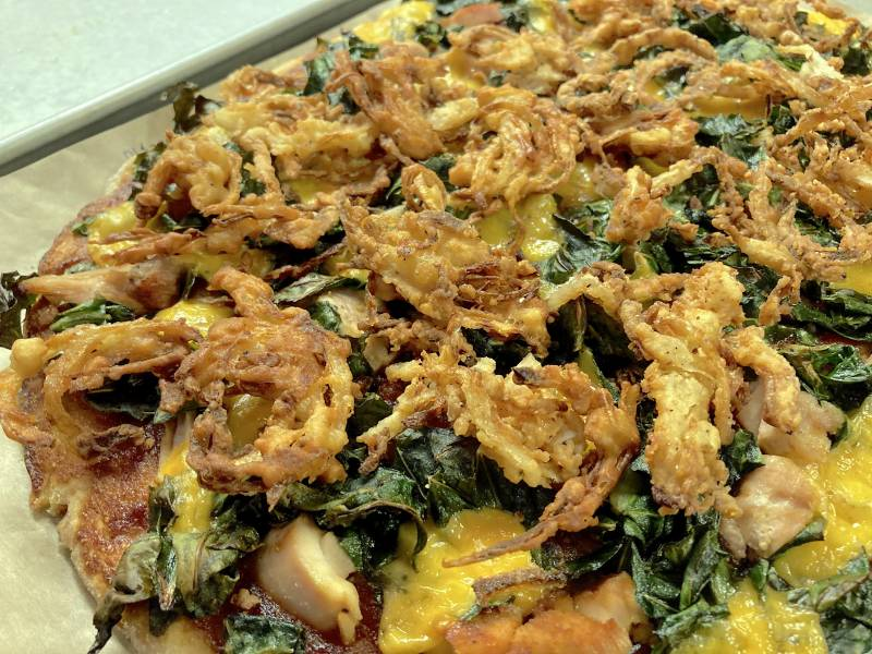 A biscuit crust pizza topped with crispy onions and collard greens.
