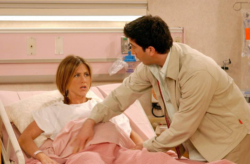 A pregnant Rachel (Jennifer Aniston) lies in a hospital bed, with Ross (David Schwimmer) at her bedside..