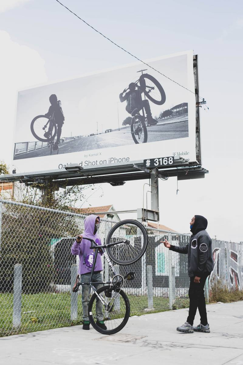 """Omar """"Meez"""" Jones and Pershanté Hill standing on 7th Street in West Oakland, talking to each other in front of a billboard that features Jones' image."""