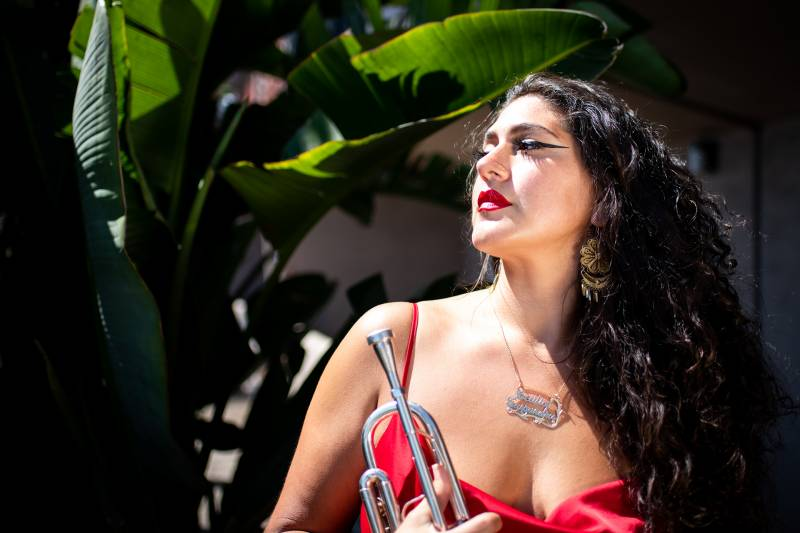 A Mexican American woman in a red dress and black eyeline holds a trumpet among tropical plants.