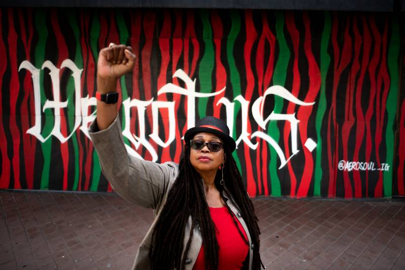 """Ayodele Nzinga raises her fist in front of a mural that says, """"We Got Us"""" by the organization AeroSoul in Oakland on July 19, 2021."""