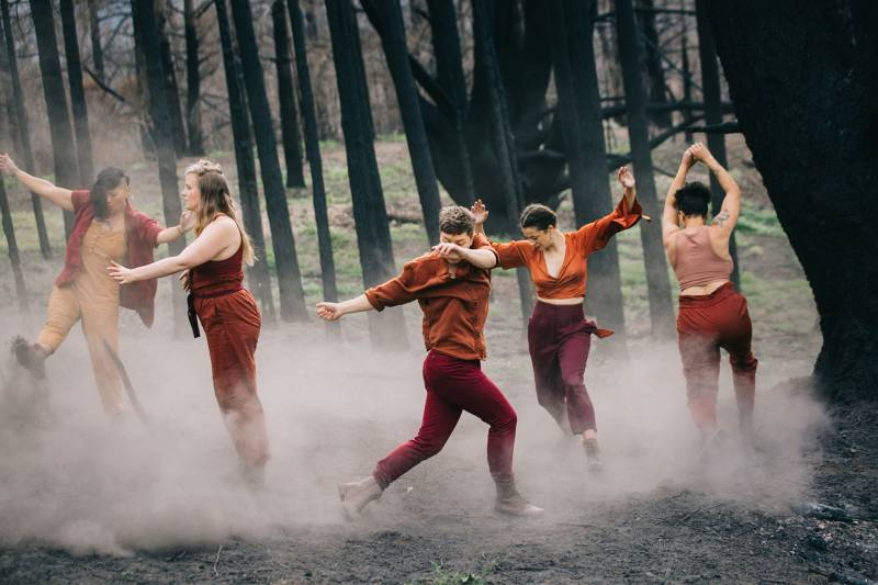 Dancers kick up ash and dust among burned trees in the mountains