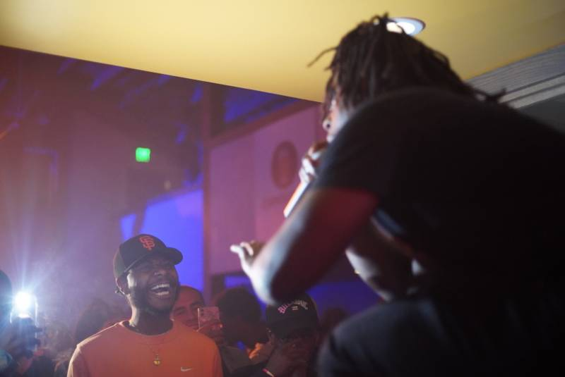 A fan in a San Francisco Giants hat takes in Stunnaman02's performance, as the emcee perches on the bar in the back of the venue.