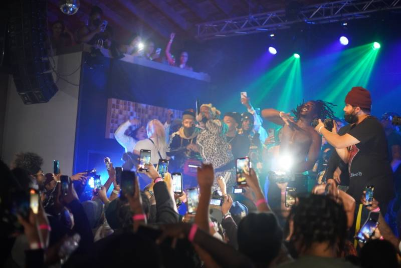 Attendees hold up their phones, capturing footage of Nef The Pharaoh performing at Cornerstone in Berkeley.