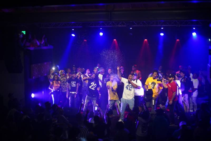 10 Piece Tone and Boss Life Big Spence perform as DJ Meles sprays a bottle of champagne on the crowd.