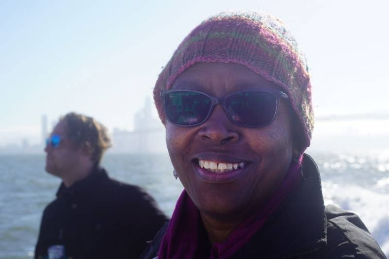 Dorothy Lazard wearing a knit cap and sunglasses, on a boat, with the SF skyline in the background