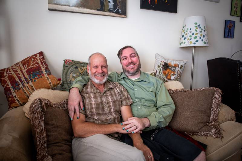 Ron (left) and Erik (right) hold each other, sitting on a couch in their home while posing for a photo.