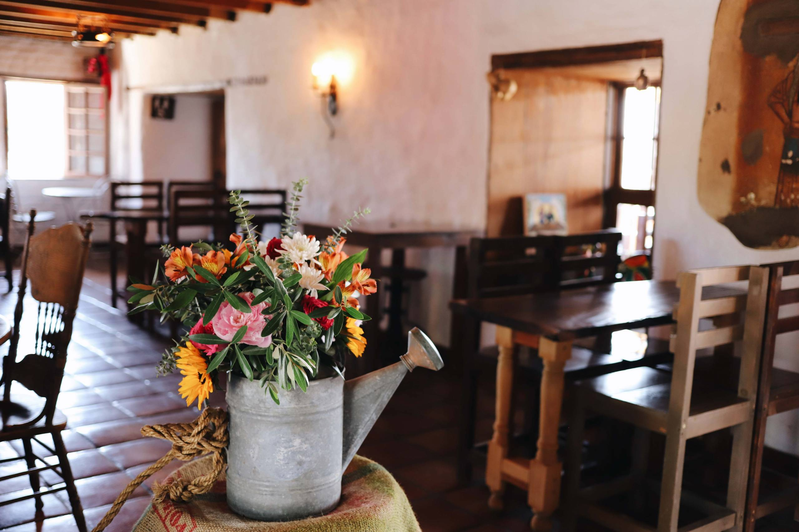 The dining room at La Cheve, with the old adobo walls and a bunch of flowers in a watering can.