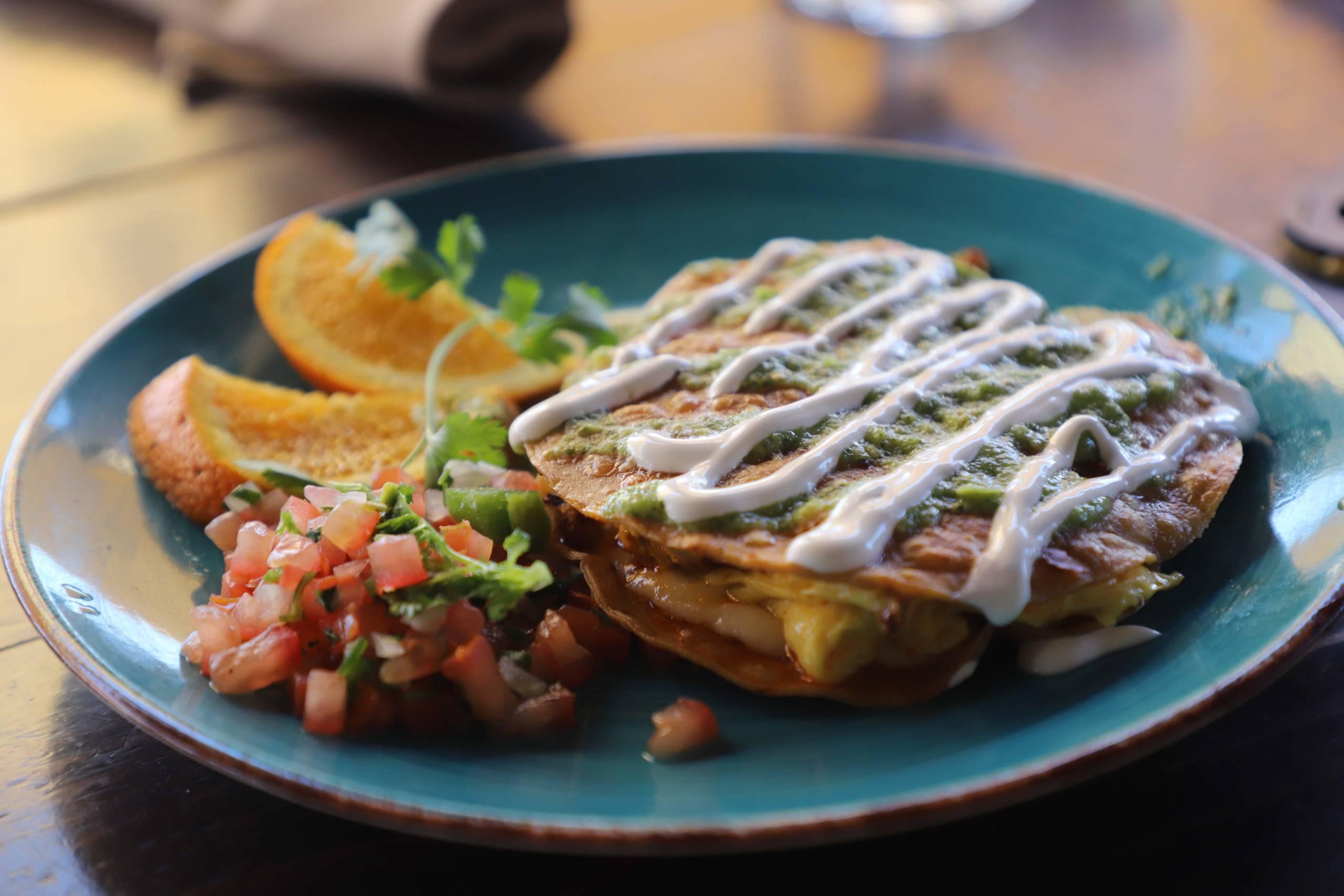 The mulita de chorizo, streaked with crema, with pico de gallo and slices of orange on the side.