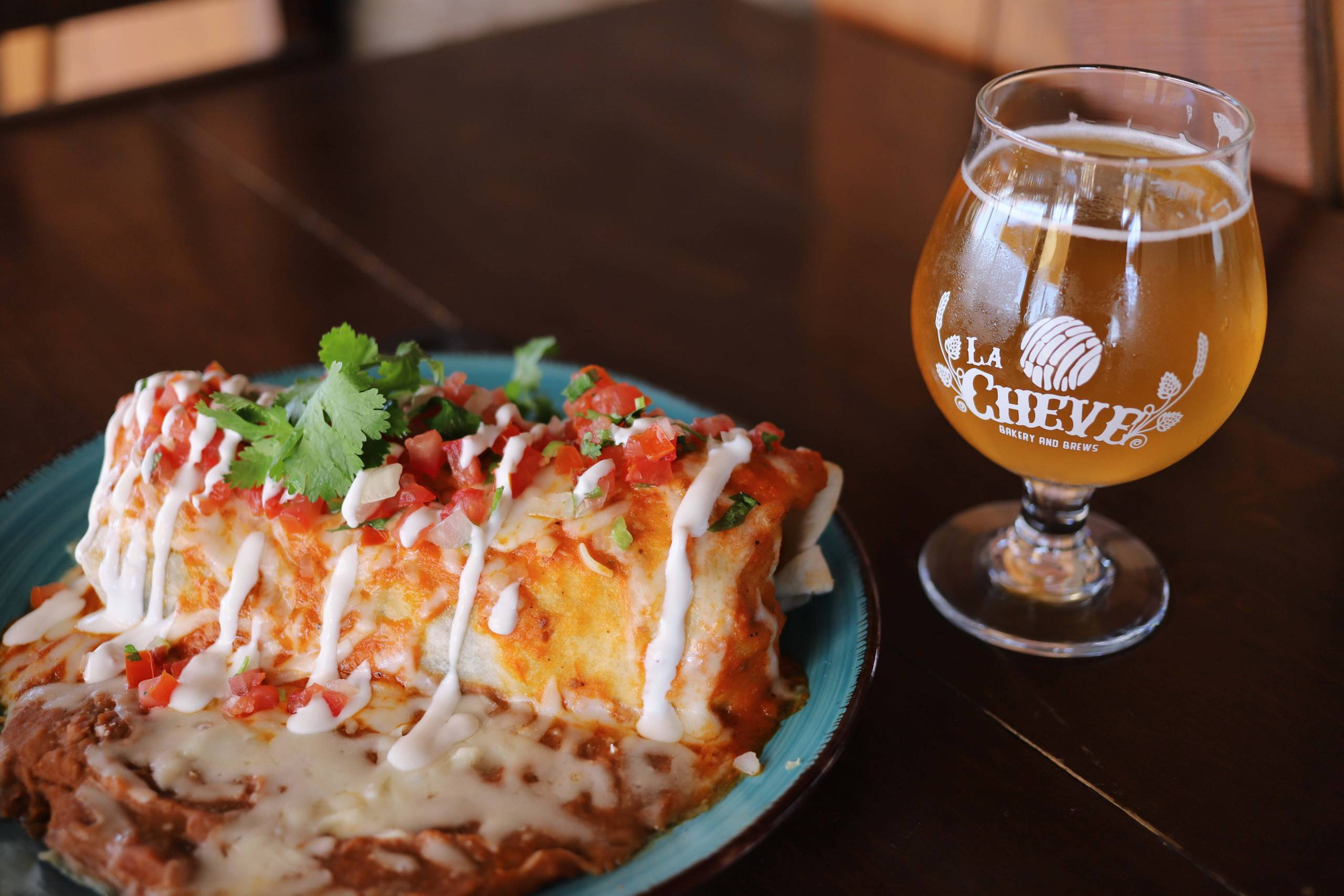A sauce-soaked burrito de chile relleno and a glass of beer.
