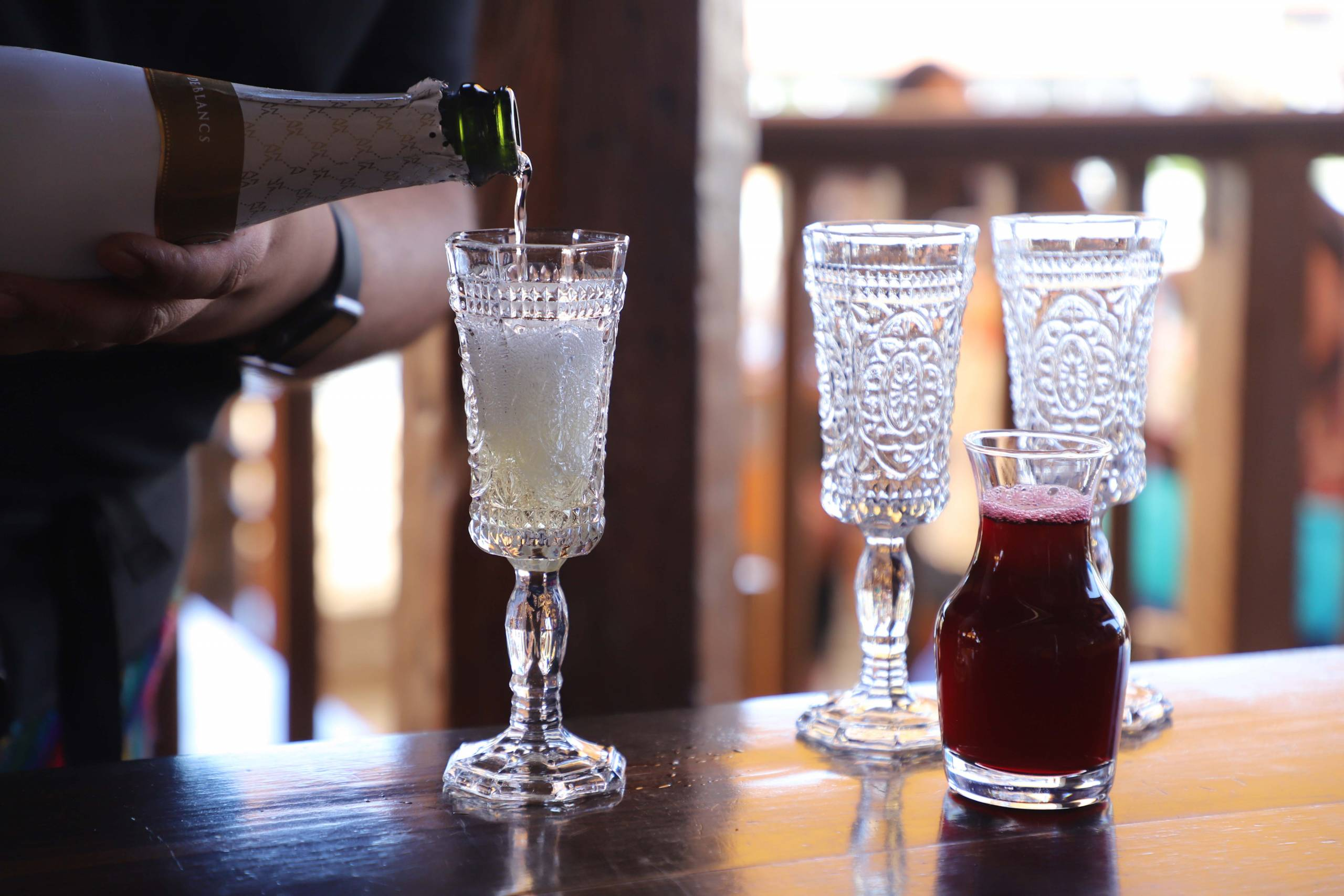 Wine being poured into a glass, with a small pitcher of hibiscus mimosa to the side.