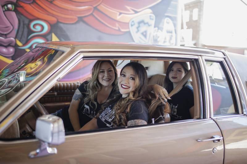 Three members of the Dueñas Car Club sit in a beige lowrider.