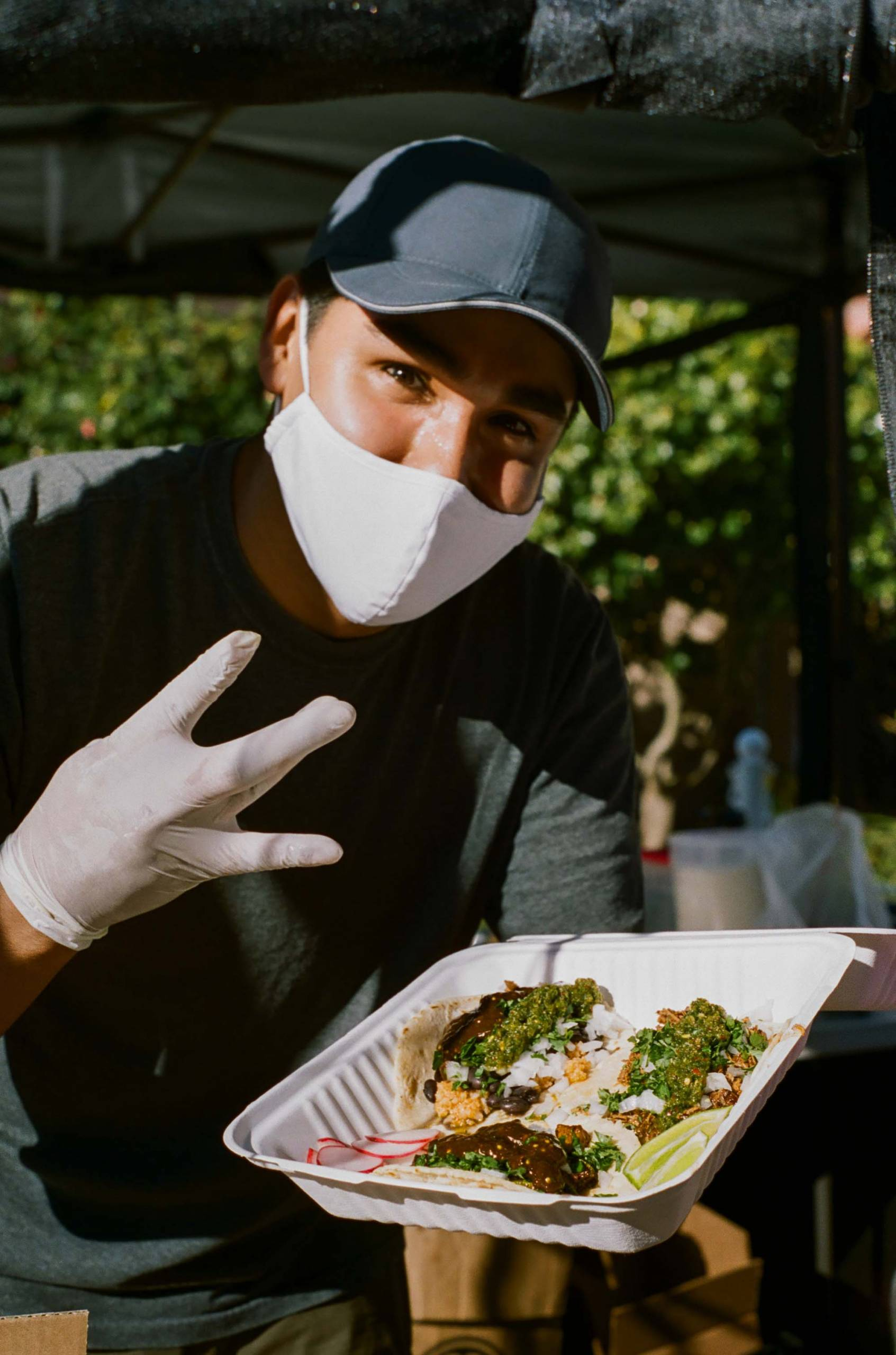 Nomar Ramirez serves up a box of tacos at his farmers market stand in the Outer Sunset
