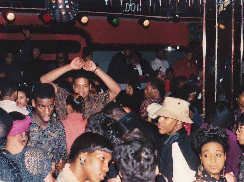 Interior shot of mostly African American crowd dancing in a crowded club in the late 1980's.