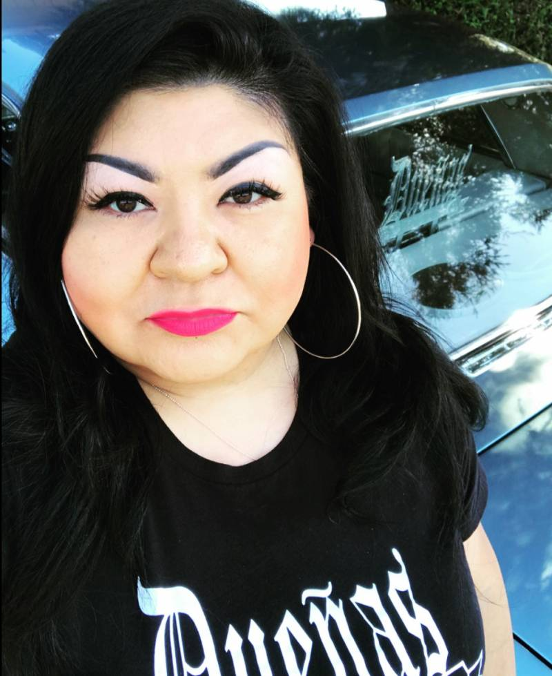 Angel Romero, the founder of the Dueñas Car Club, takes a selfie in front of her car, through the window you can see the Dueñas logo, it's also on her black t-shirt.