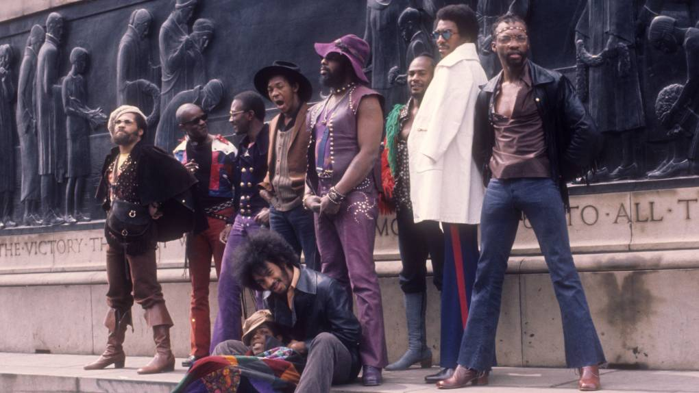 """LIVERPOOL, ENGLAND - MAY 1971: (L-R) Fuzzy Haskins, Tawl Ross, Bernie Worrell, Tiki Fulwood, Grady Thomas, George Clinton, Ray Davis, Calvin Simon and seated Eddie Hazel and Billy """"Bass"""" Nelson of the funk band Parliament-Funkadelic pose for a portrait in May 1971 in Liverpool, England. (Photo by Michael Ochs Archives/Getty Images)"""