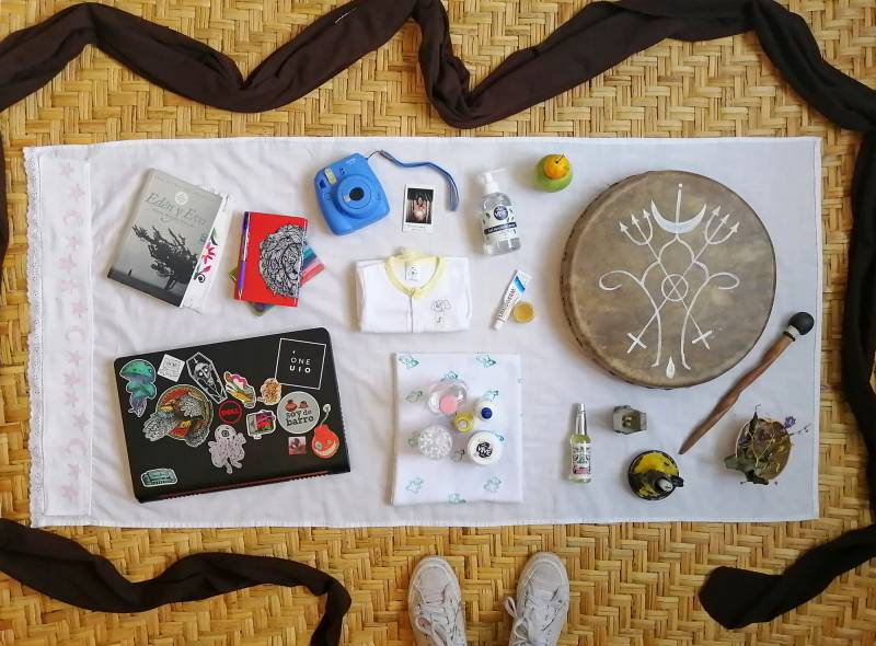 Items, left to right: Book, notebooks, laptop, instant camera with print, baby clothes, personal hygiene supplies for mother and baby, hand sanitizer, local fruits, ointment, shamanic drum, Agua de Florida ritual water, prayer altar, spiritual candle, herbs. Also pictured: a black baby wrap surrounds the items with the photographer's shoes visible.