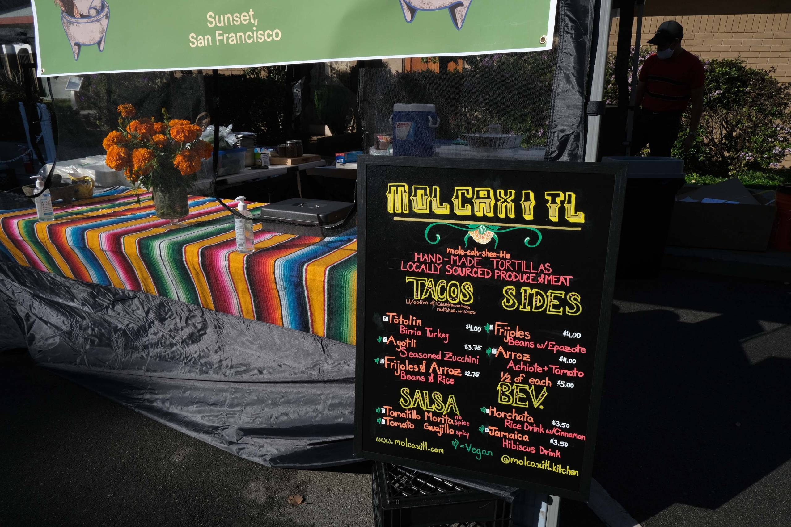 The menu board for Molcaxitl set up in front of the Outer Sunset farmers market stand