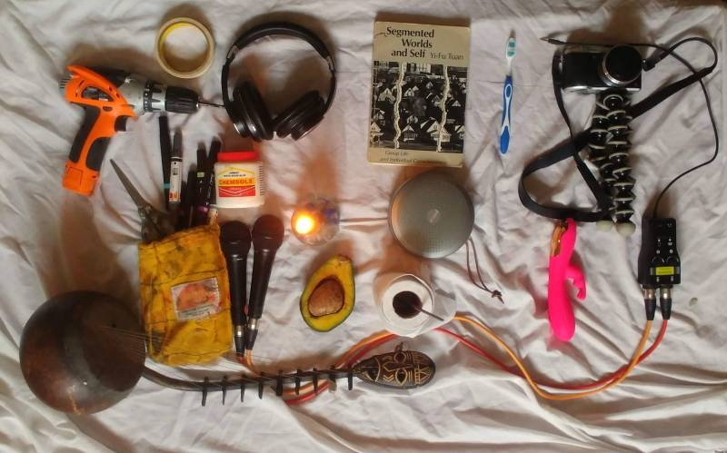Items left to right: Drill, masking tape, headphones, collage-making supplies, microphones, kora (a type of lute), avocado, toilet paper, speaker, book, toothbrush, camera, vibrator.