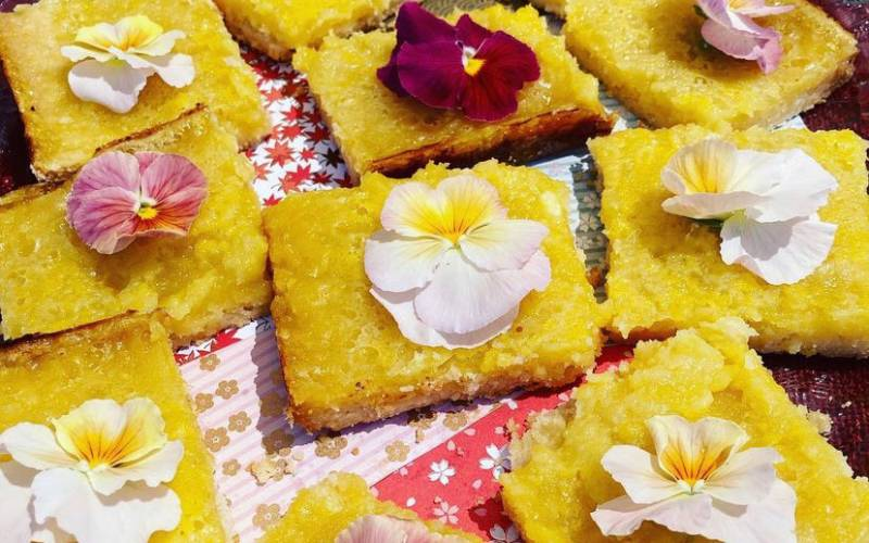 A spread of lemon bars topped with pink and red edible flowers.