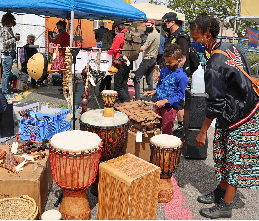 A young child tries playing African drums at an outdoor market.