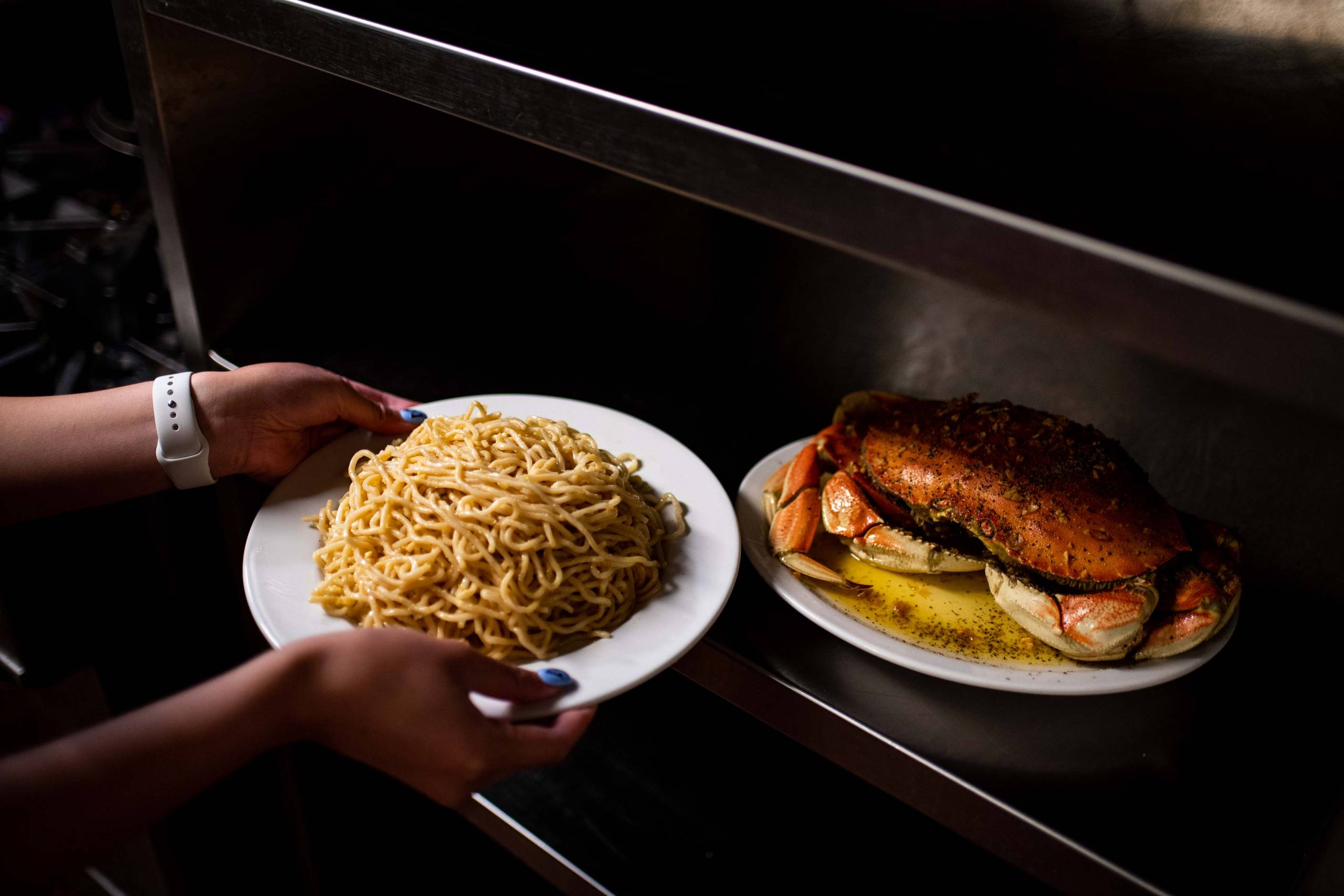 A server picks up a plate of garlic noodles and a whole Dungeness crab from Thanh Long's hidden kitchen inside the main kitchen.