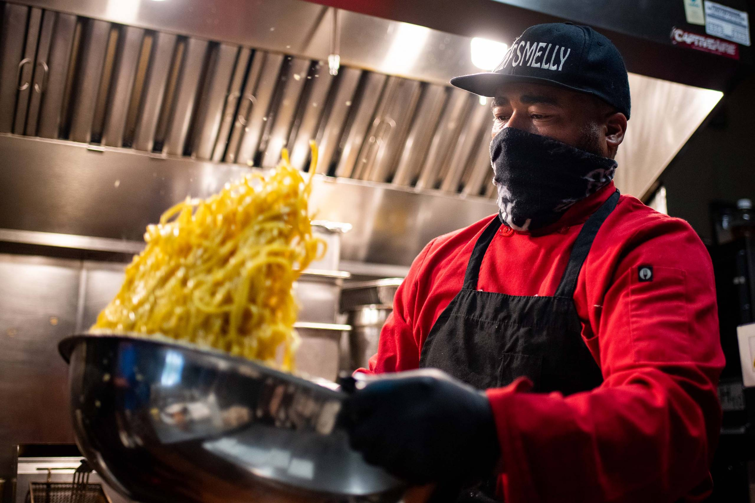 Chef Edward Wooley tosses a batch of garlic noodles in a large metal bowl.