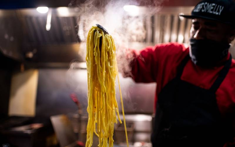 A chef holding a large tangle of steaming garlic noodles with a pair of tongs.