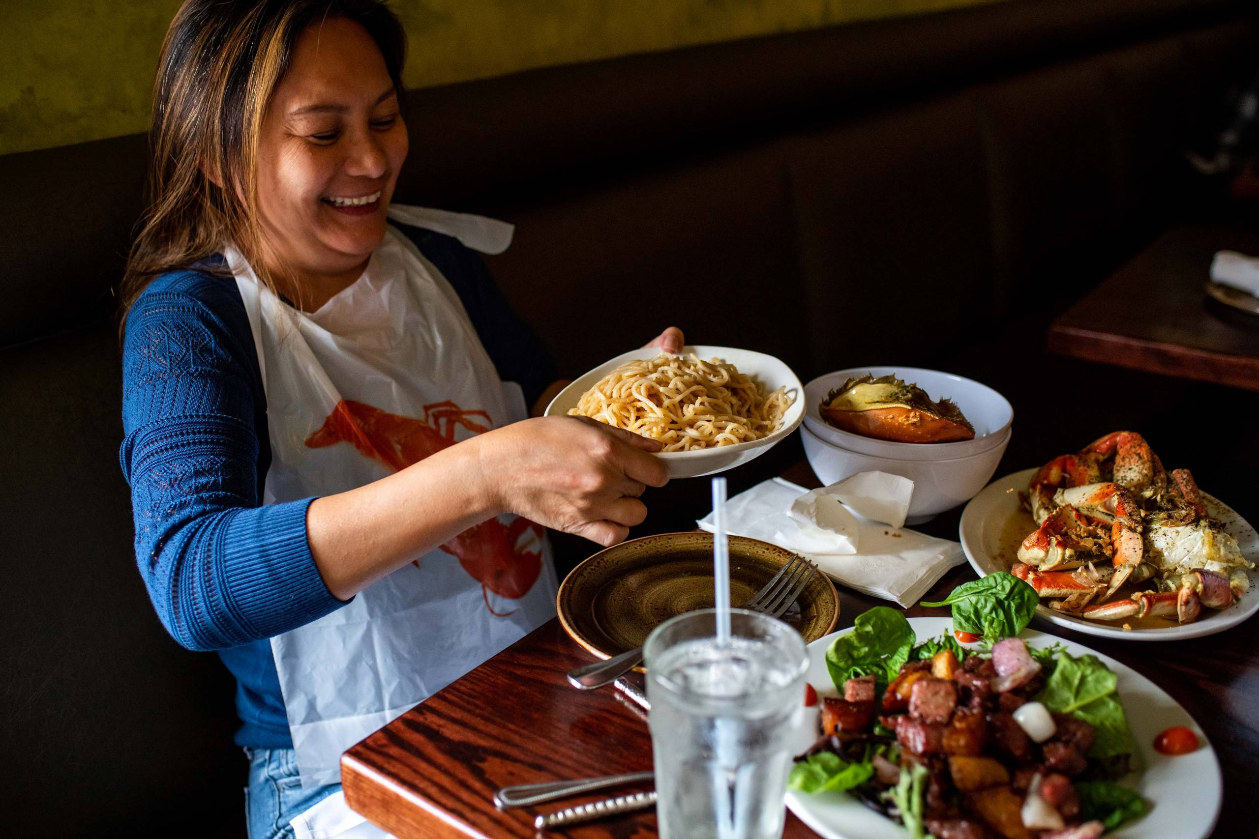 A customer wearing a plastic bib prepares to dig in to a plate of garlic noodles.