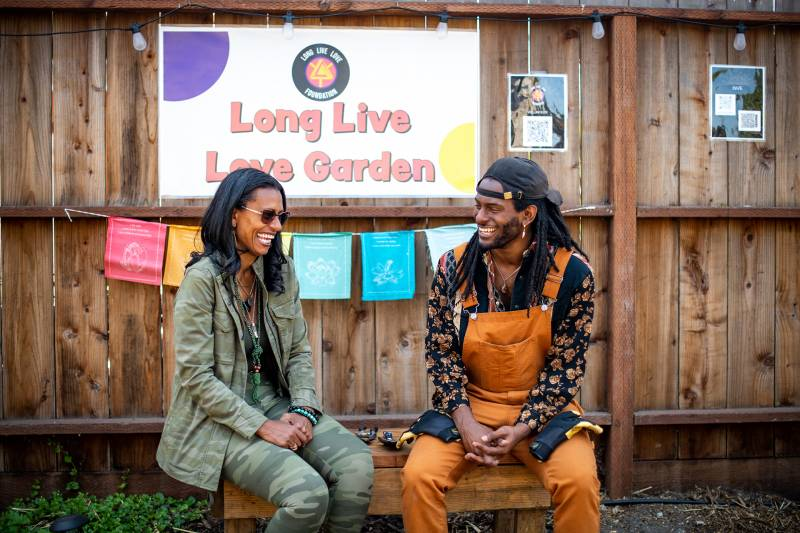 """A woman and her adult son laugh together in front of a wooden gate with a sign that reads """"Long Live Love Garden."""""""